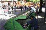 1 de maig a Girona Un home busca alguna cosa de valor a l'interior d'un contenidor mentre la manifestació del Primer de Maig a Girona passa per la Gran Via Jaume I