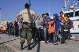 Arribada dels refugiats sirians a l'illa de Kos  Un militar controla un grup de sirians interceptats en una petita embarcació al mar.