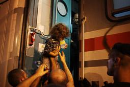 Refugiats sirians a la frontera Sèrbia-Croàcia Uns homes ajuden a pujar una nena al tren que els durà cap a la frontera hongaresa per anar després a Àustria. Foto: Sergi Cámara