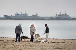 Eleccions andaluses 2015 Veïns de Rota passegen els seus gossos per la platja, amb els vaixells de la base naval de fons.