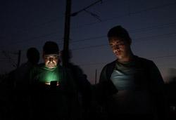 El drama dels refugiats sirians, a la frontera de Macedònia Dos refugiats mirant el mòbil mentre esperen a la frontera (25 d'agost). Foto: Sergi Cámara