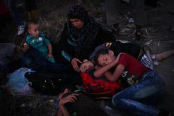 El drama dels refugiats sirians, a la frontera de Macedònia Una família descansa després d'arribar a la frontera i afegir-se als centenars de persones que esperen per travessar-la (25 d'agost). Foto: Sergi Cámara