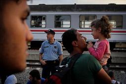 Refugiats sirians a la frontera Sèrbia-Croàcia Un pare juga amb la seva filla mentre espera pujar al tren des de Croàcia. Foto: Sergi Cámara