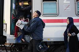 Refugiats sirians a la frontera Sèrbia-Croàcia Un policia croat ajuda una dona a portar el seu fill. Foto: Sergi Cámara