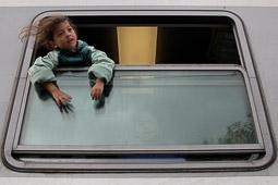 Refugiats sirians a la frontera Sèrbia-Croàcia Una nena siriana juga des de la finestra del tren que la durà cap a Hongria. Foto: Sergi Cámara
