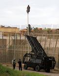 Melilla, el mur d'Europa Divendres 28 de març / Un subsaharià, enfilat al capdamunt d'una farola.