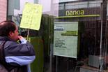Les PAH d'arreu de Catalunya ocupen seus de Bankia Un home protesta davant l'oficina de Bankia a Tarragona. Foto: Roger Segura