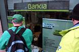 Les PAH d'arreu de Catalunya ocupen seus de Bankia Dos membres de la PAH observen l'interior de l'oficina de Bankia a Tarragona, tancada, i atenent clients. Foto: Roger Segura