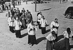 Revolució, guerra i franquisme a Vic Comitiva religiosa amb el bisbe Joan Perelló, acompanyat d'un oficial de la Guàrdia Civil.